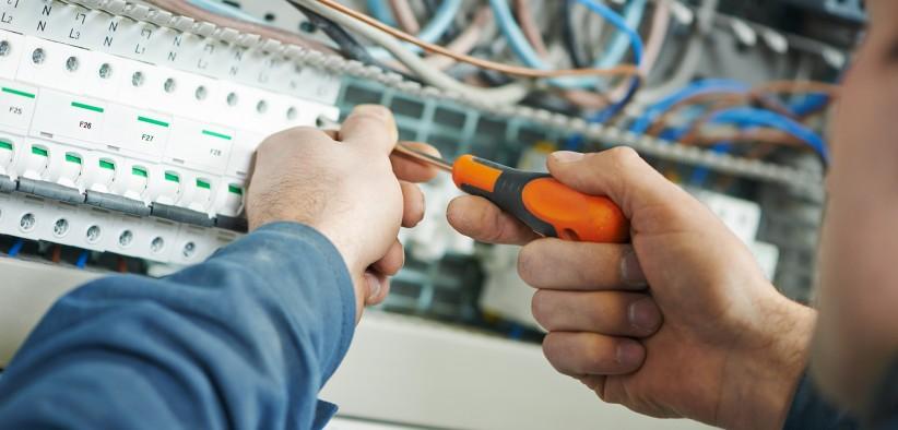 Électricien qui réalise les branchements d'une armoire électrique