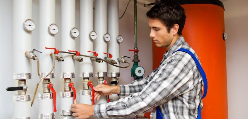 Jeune ingénieur chauffagiste qui règle le système de chauffage de la chaudière